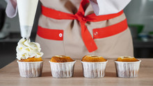 Pastry Chef Decorates Cupcakes In Paper Cups White Cream With Pastry Bag. Hands Close-up. Front View