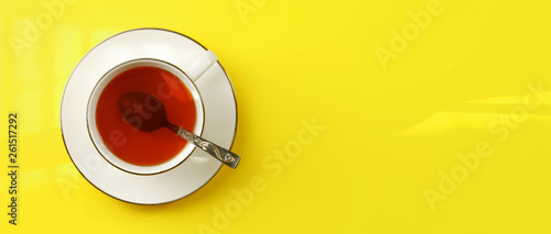 Fotografie, Obraz  Flat lay photo - white porcelain cup with spoon filled hot amber tea, on yellow