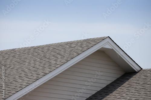Foto  Roof shingles on top of the house against blue sky with cloud, dark asphalt tile