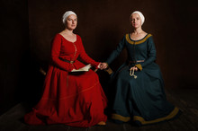 Two Sisters (twins) In Medieval Costumes Play The Nobility. Evening Reading Of The Prayer (bible).