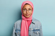 Leinwanddruck Bild - Close up shot of good looking woman with healthy skin, wears transparent glasses, pink scarf on head, jean jacket, isolated over blue background, has confident gaze at camera. Religion concept