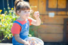 Adorable Little Girl Holding Basket Full Of White And Brown Raw Eggs