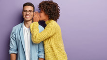 Afro American Female Whispers Secret To Boyfriend Who Has Cheerful Expression, Gossip Together, Wear Casual Clothes, Stands Against Purple Background With Blank Space. Diverse Couple Indoor.