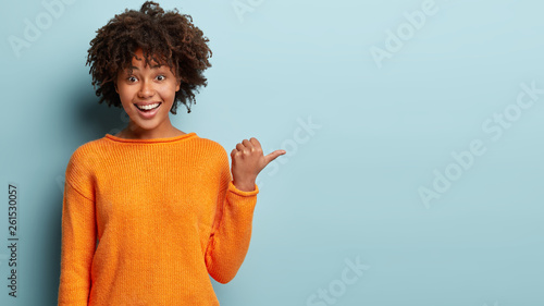 Fotografie, Obraz  Photo of delighted cheerful Afro American woman with crisp hair, points away, sh