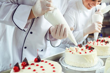 Two Pastry Chefs Decorate A Cake From A Bag In A Pastry Shop