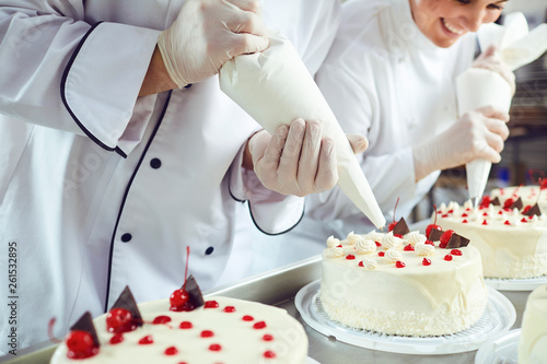 Fotografia, Obraz  Two pastry chefs decorate a cake from a bag in a pastry shop