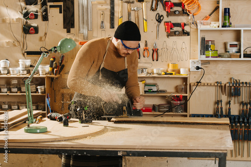 Fotografie, Obraz  Carpenter is making furniture on order in a workshop.