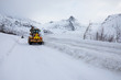 Snow plow truck clearing icy road after winter snowstorm blizzard for vehicle access Snow blower clears snow-covered streets producing a plume of snow. Winter landscape in Norway or Sweden Scandinavia