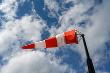 Windsock Over Blue And Cloudy Sky