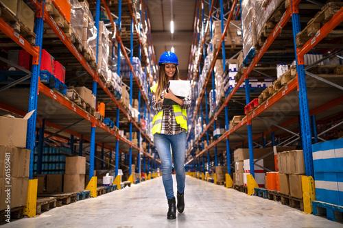 Fotografía  Portrait of confident female worker walking through distribution warehouse