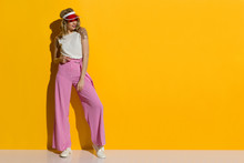 Smiling Fashion Model In Striped Wide Legs Trousers And Transparent Sun Visor Is Standing In The Sunlight