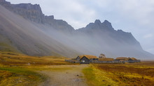 A Small Abandoned Vikings Village. Sod Rooftops, Turf Rooftops. Village Located At The Bottom Of A High Mountain. Around The Farm A Wooden Fence. Dry Grass All Around. Tall Mountains Being A Shelter.