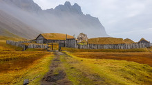 An Abandoned Vikings Village. Sod Rooftops, Turf Rooftops. Village Located At The Bottom Of A High Mountain. Around The Farm A Wooden Fence. Dry Grass All Around. Traditional Scandinavian Architecture