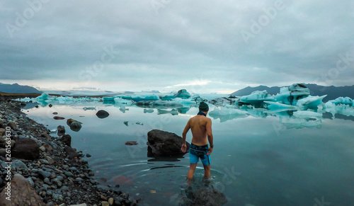 Photo Young man enters the icy cold waters of Glacier lagoon