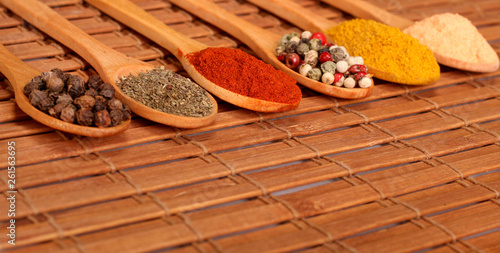 Group of indian spices and herbs difference ware in wooden spoons on wooden back Canvas Print