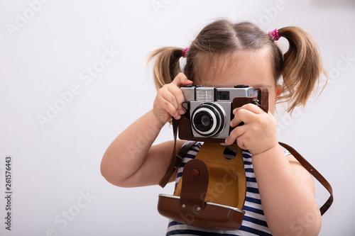 Obraz Little Girl Taking Picture Using Photo Camera - fototapety do salonu