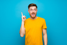 Redhead Man Over Blue Wall Intending To Realizes The Solution While Lifting A Finger Up