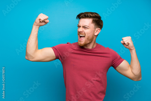 Fotografía Redhead man on isolated blue wall celebrating a victory