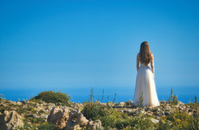 A Bride In A White Wedding Dress Standing On A Cliff Edge Looking Out To Sea