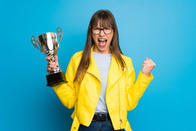 Young Woman With Yellow Jacket On Blue Background Holding A Trophy