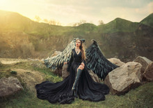 Revived Gargoyle, Queen Of Night Watching Sunrise, Girl In Long Light Black Dress With Black Feather Wings Sits On Rocks With Open Leg In High Boots, Mysterious Mythical Creature, Creative Art Photo