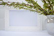 White frame with green willow branches on a white background. Copy space in the middle for your text.