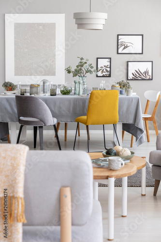 Grey And Mustard Chairs Placed By The Dining Table With Fresh Plants
