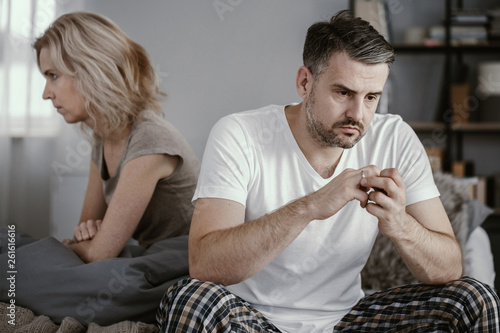 Leinwand Poster Man in pajamas sitting in bed and taking off his wedding ring after his wife ann