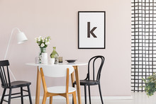 Poster In Black Frame On Pastel Pink Wall Of Sophisticated Dining Room Interior With Round Table