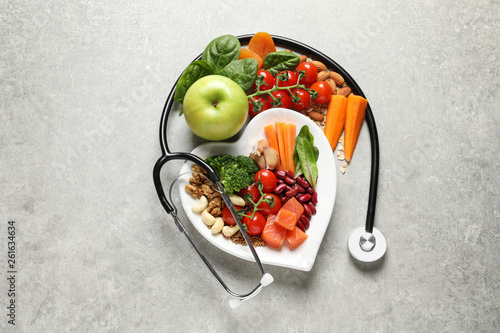 Flat lay composition with plate of products for heart-healthy diet on grey background