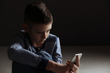 Upset Boy With Smartphone Sitting Indoors. Space For Text