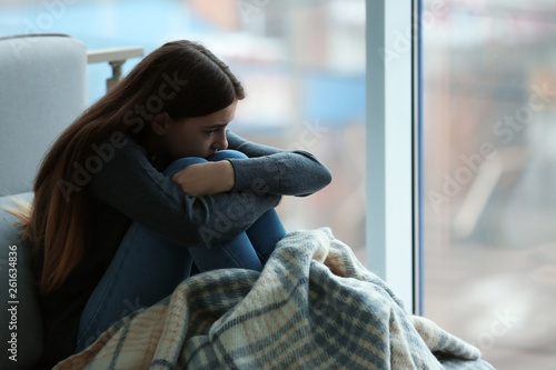 Upset teenage girl sitting at window indoors. Space for text