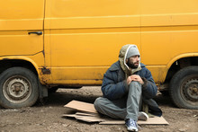 Poor Homeless Man Sitting Near Van Outdoors
