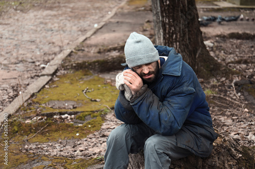 Fotografía  Poor homeless man sitting on stump outdoors