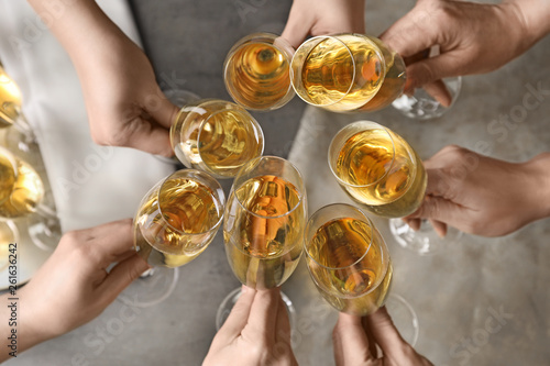 Fotografia People clinking glasses with champagne over table, top view