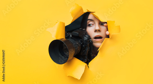 A young paparazzi girl with a reflex camera looks out from cover and looks at what is happening with her mouth open. Yellow paper, torn hole. Tabloid press. In search of the plot for photo stocks.