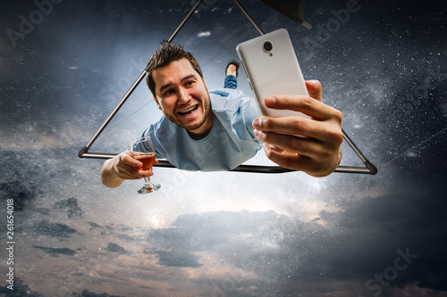 Fotografía  Young man flying on hang glider. Mixed media