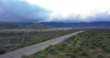 Aerial, cars traveling through spring bloom desert of Anza Borrego State Park, Storm clouds gathering in distance