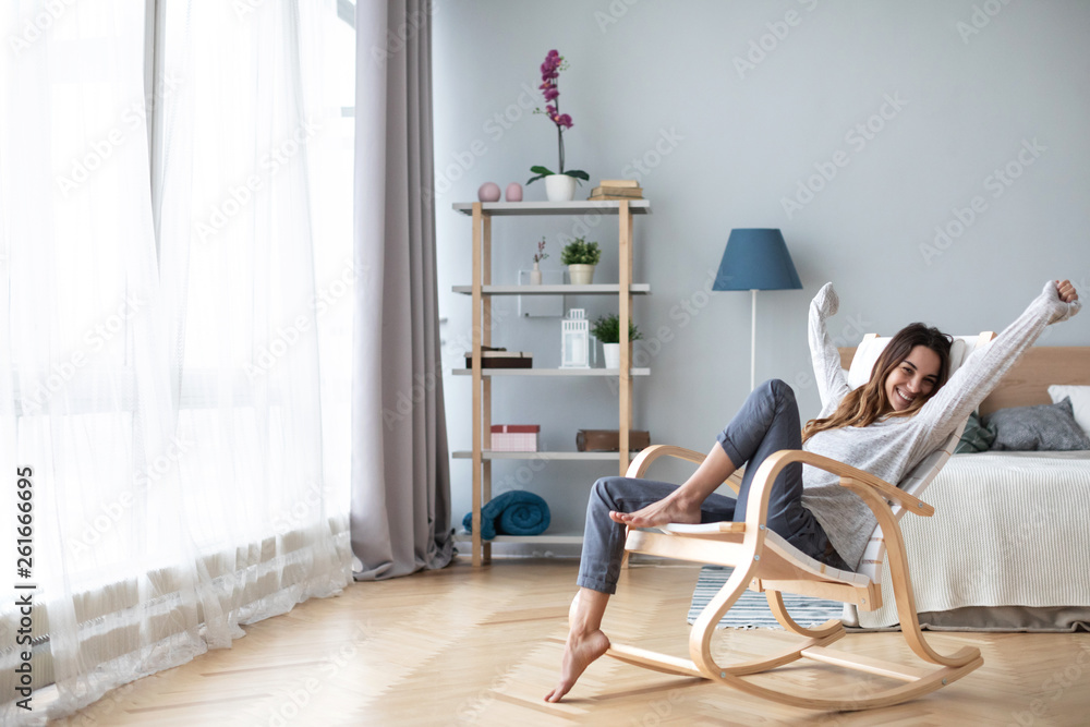 Fototapety, obrazy: Happy woman resting comfortably sitting on modern chair in the living room at home.