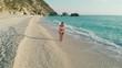Aerial - Beautiful adult woman in a bikini walking barefoot in the water
