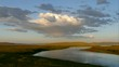 Small river on a plain against the distant hills and picturesque sky.Timelapse.