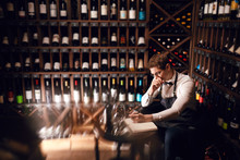 Thoughtful Male Sommelier Looking At A Very Wide Range Of Wines From The Main Regions Of The World Placed Of Wine Shelves, Writing In Note Pad Some Things Working At Wine Restaurant.