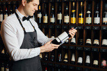 Young Caucasian Cavist Dressed In White Shirt And Bowtie Working In Big Vine Shop Presenting A Bottle Of Red Wine To Customer