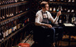 Cavist at store, sommelier at restaurant, critic. Wine Degustation. tasting experience in the club, man holding a glass of delicious wine.