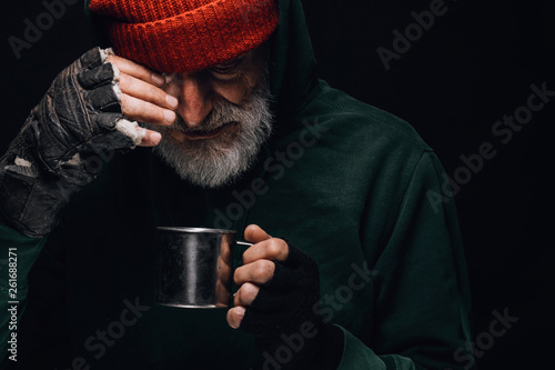 Fotografia, Obraz Old homeless man with grey beard covering up in green decrepit clothes holding a