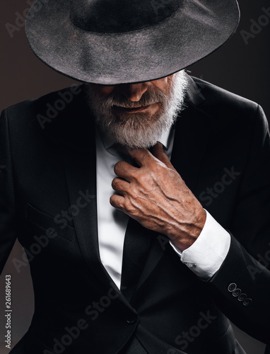 Fotografie, Obraz  An old male actor playing an English spy role, dressed in black suit, hiding behind fedora hat, having mysterious elegant look