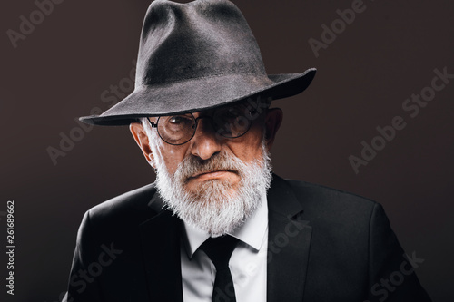 Fotografie, Obraz  Old-aged bearded man in image of English secret agent wearing black suit with hat on his eyes posing against dark background