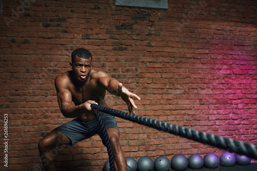 Fotografie, Obraz  African man with naked torso doing fitness workout in cross fit gym