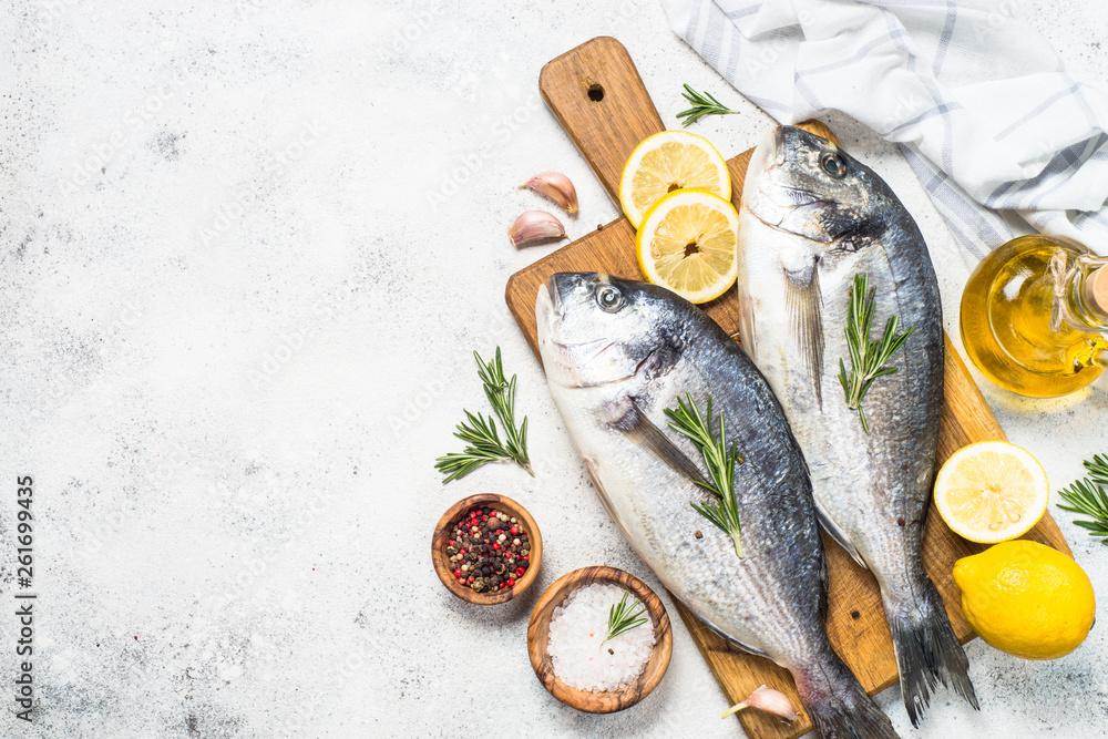 Fototapeta Raw dorado fish on cutting board on the table.