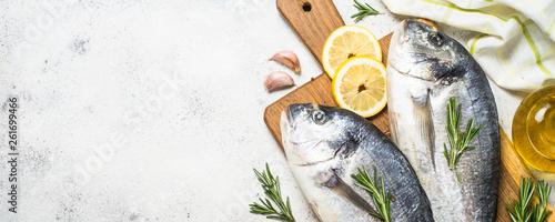 Raw dorado fish on cutting board on the table. Tablou Canvas